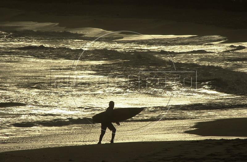 A surfer walks on a beach of Rio de Janeiro. (AustralFoto/Douglas Engle)