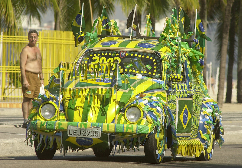 """A Brazilian football fan drives a Volkswagen bug, known as a """"fusca"""" in Brazil, in Copacabana section of Rio de Janeiro, in this photo taken June 12, 2002, during the World Cup. (AustralFoto/Douglas Engle)"""
