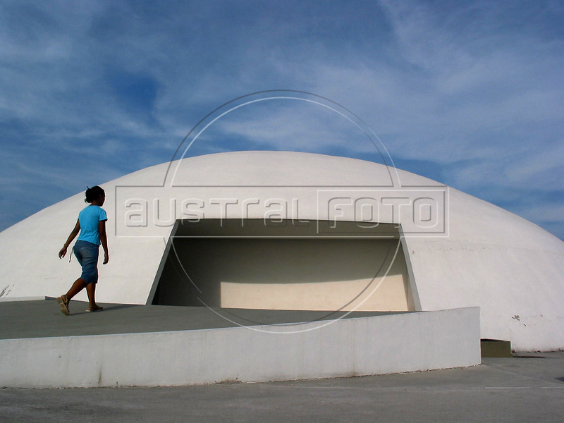 A guide walks into the Roberto Silveira Memorial, designed by Brazilian architect Oscar Niemeyer, in Niteroi, near Rio de Janeiro, Brazil. The dome-shaped building is part of a complex of buildings under construction at the Niteroi waterfront. Niemeyer is known for his futuristic round and curving designs, and in particular for designing most of the buildings in Brasilia, the planned Brazilian capital. Born in Rio de Janeiro in 1907, Niemeyer's formative experience was in 1934 when he joined a team of Brazilian architects collaborating with French architect Le Corbusier on a new Ministry of Education and Health in Rio de Janeiro. It was while working on this project that he met the mayor of Brazil's wealthy central state, Juscelino Kubitschek, who would later become President of Brazil. As President, he appointed Niemeyer to be the chief architect of Brasilia, a project which occupied all of his time for many years. (AustralFoto/Douglas Engle)
