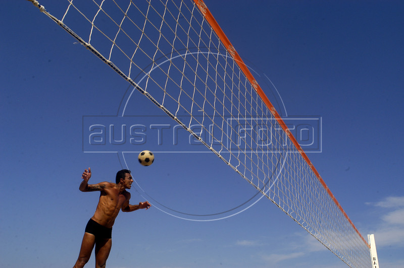 """A beach goer plays """"foot-volley,"""" a uniquely Brazilian sport which combines soccer skills with a volleyball court, on a beach of Rio de Janeiro. (AustralFoto/Douglas Engle)"""