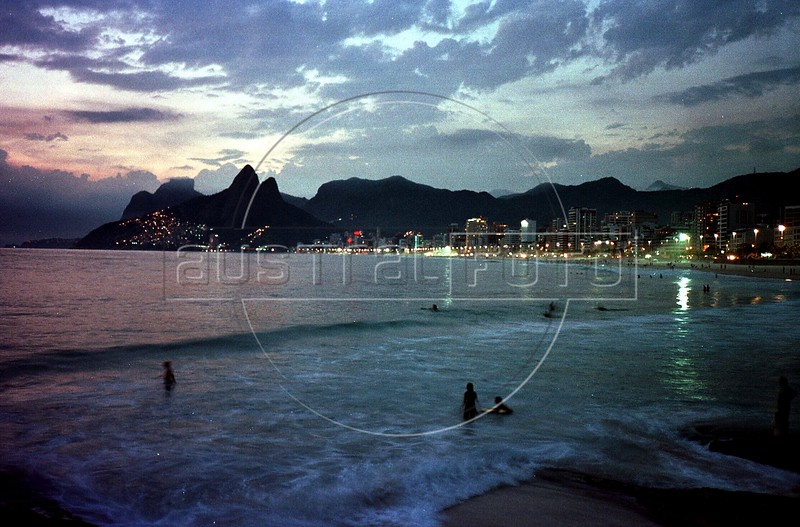 Sun sets behind the Two Brothers mountain on Ipanema Beach in Rio de Janeiro. (AustralFoto/Douglas Engle)