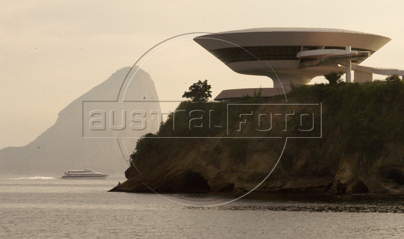 The Contemporary Art Museum (MAC), designed by Brazilian architect Oscar Niemeyer, sits on a hill in Niteroi, as the famous Sugarloaf mountain of Rio de Janeiro, rises above the Guanabara Bay in the background. Niemeyer is known for his futuristic round and curving designs, and in particular for designing most of the buildings in Brasilia, the planned Brazilian capital. Born in Rio de Janeiro in 1907, Niemeyer's formative experience was in 1934 when he joined a team of Brazilian architects collaborating with French architect Le Corbusier on a new Ministry of Education and Health in Rio de Janeiro. It was while working on this project that he met the mayor of Brazil's wealthy central state, Juscelino Kubitschek, who would later become President of Brazil. As President, he appointed Niemeyer to be the chief architect of Brasilia, a project which occupied all of his time for many years. (AustralFoto/Douglas Engle)