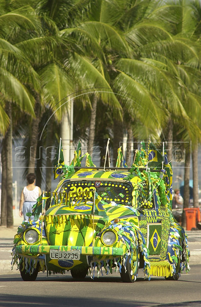 "A Brazilian football fan drives a Volkswagen bug, known as a ""fusca"" in Brazil, in Copacabana section of Rio de Janeiro, in this photo taken June 12, 2002, during the World Cup. (AustralFoto/Douglas Engle)"