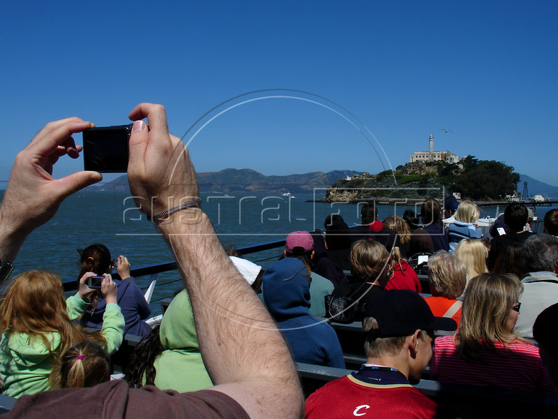 A tourist takes a snapshot of San Francisco's most popular attractions, Alcatraz Island. The small island located in the middle of San Francisco Bay served as a lighthouse, then a military fortification, then a military prison, followed by a federal prison. In 1963, it became a national recreation area. Today, the island is a historic site supervised by the National Park Service .(Australfoto/Douglas Engle)