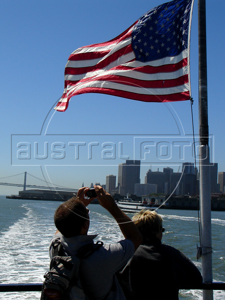 Tourists photograph the American flag on a Ferry in the San Francisco Bay, with the San Francisco skyline in the background.(Australfoto/Douglas Engle)