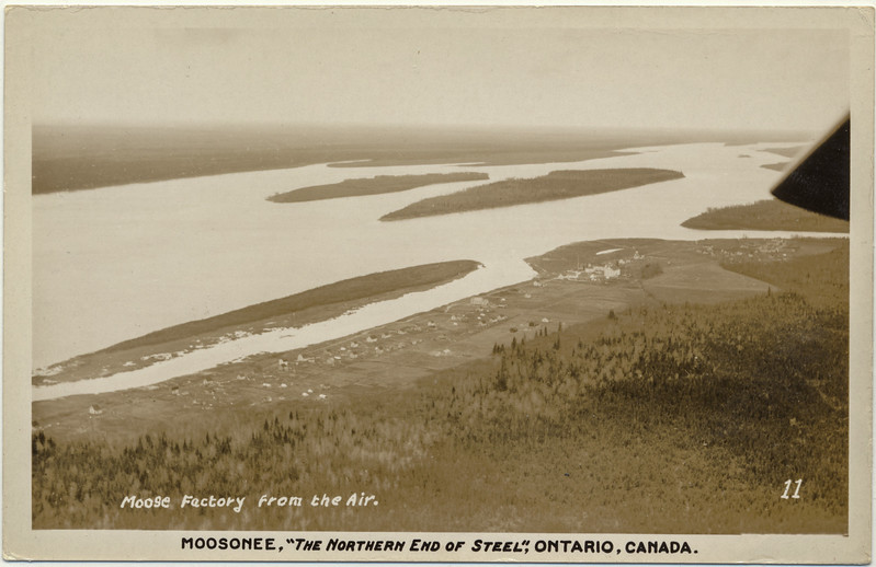 """Postcard: Moose Factory from the air. From series """"Moosonee the Northern end of Steel, Ontario, Canada"""" 11. Undated. Aerial view of Moosonee looking southwest. This folder contains a better version of this postcard."""