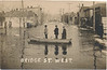 """Postcard: Belleville, Ontario. Bridge Street West facing East towards downtown, Bridge Street Methodist (United) Church visible. Undated. Flooding, ice chunks on street. Three men in a board in middle of the street. Back of card says """"This is the City of Belleville. It gives you some idea what it is like when it is cold and a mess when it melts"""". Appears to be barricade across bridge."""