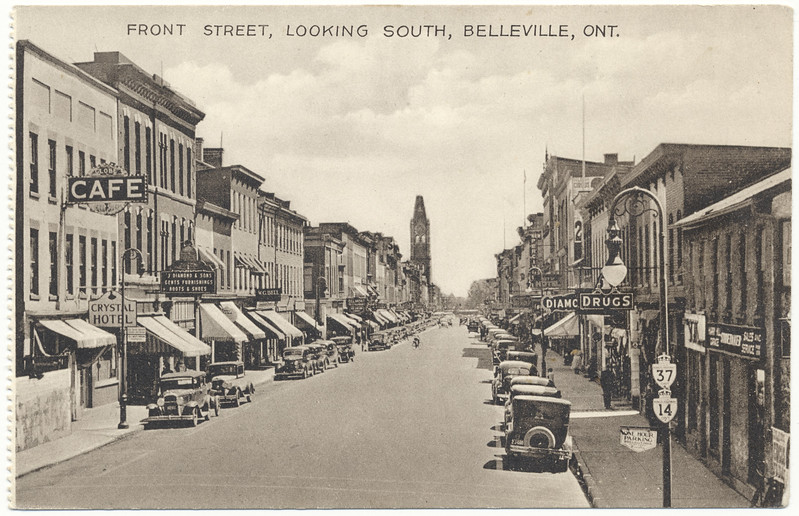 Postcard: Belleville, Ontario. Front Street Looking South. City Hall in distance. Signs for Highways 37 and 14. Crystal Hotel, J. Diamond and Sons Gents Furnishings Boots and Shoes, Belmont Restaurant, W.G. Bell, Globe Cafe, Unused, Undated.