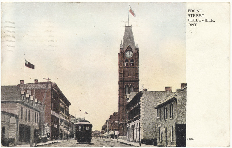 "Postcard: Belleville, Ontario. Front Street looking north past City Hall. Dated 1907 July 9th. Written in French to Quebec address. Streetcar on Front Street. ""Red Ensign"" flags."