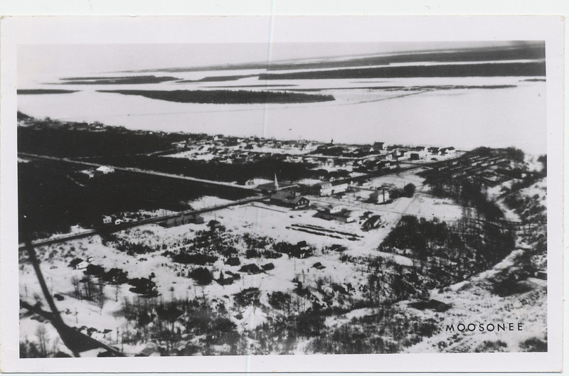 Postcard: Moosonee. Aerial view, no date. Wing struts visible.