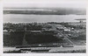 Postcard, black and white, aerial, Moosonee, Ontario, taken from past railroad station looking towards river. Undated, unmailed