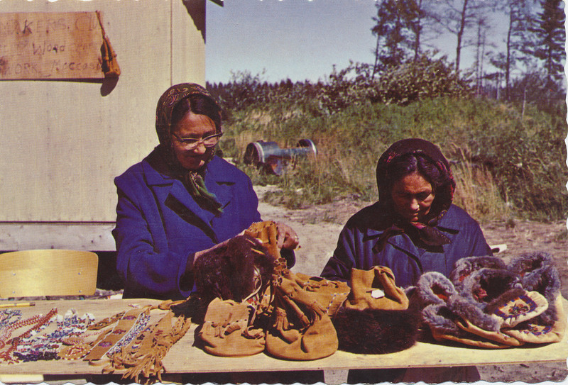 Postcard: Two women with crafts. Myriah Wynne and Hannah Chakasim. Sign says Homemaker's Club. Mailed 1976 September 25th from Cochrane, Ontario. Message dated the previous day. Canadian 10 cent stamp.