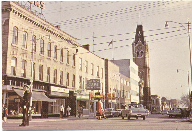 Postcard: Belleville, Ontario. Front Street looking south from four corners towards City Hall. Household Finance, Tip Top Tailors, Paragon Cafe, Pam's Hobby Shop, James Text, Victoria and Grey building, Guaranty Trust. Unused postally. Quebec address on back with postal code.