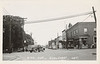 """Postcard:  4th Ave, Englehart, Ont.""""<br /> View looking towards tracks (not visible) across intersection with Third Street.<br /> Back:  Universal Photo Service Toronto Ont."""
