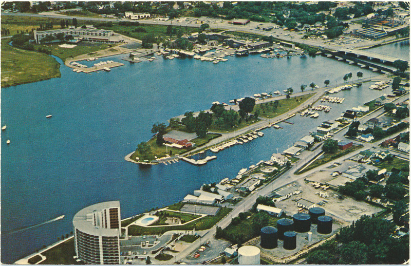 """Postcard: Aerial, Belleville, Ontario. Looking northwest from Anchorage, oil tanks, Victoria Island with Yachut Club towards Corbin Lock / International Hardware buildings at right and Four Seasons at left. Dundas Street bridge. Likely taken late 1970s. Anchorage built 1978. Unused. Reverse says """"A major yachting centre on the beautiful Bay of Quinte with full service harbour and marine facilities"""". Published by Richard Lumbers Photography."""