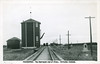 Postcard: Moosonee. Looking from Store Creek bridge to station. Showing memorial cairn, water tower for steam locomotives.