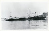 Postcard: Moosonee. Tug Churchill River, another tug, barge HBC 1010. Unused, no date but flying Canadian maple leaf flags.  Somewhat blurry.