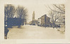 Postcard: Belleville Flood 1936 Front Street, handwritten text on back. This is the main street, the water and ice came in the backs of the stores and went out by the front door. The water was five feet deep in places. The building on the left is one of our fire halls.