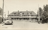 "Postcard: Englehart Ontario train station front.<br /> No text<br /> ""MacLean photo""<br /> Car in foreground parked on street."