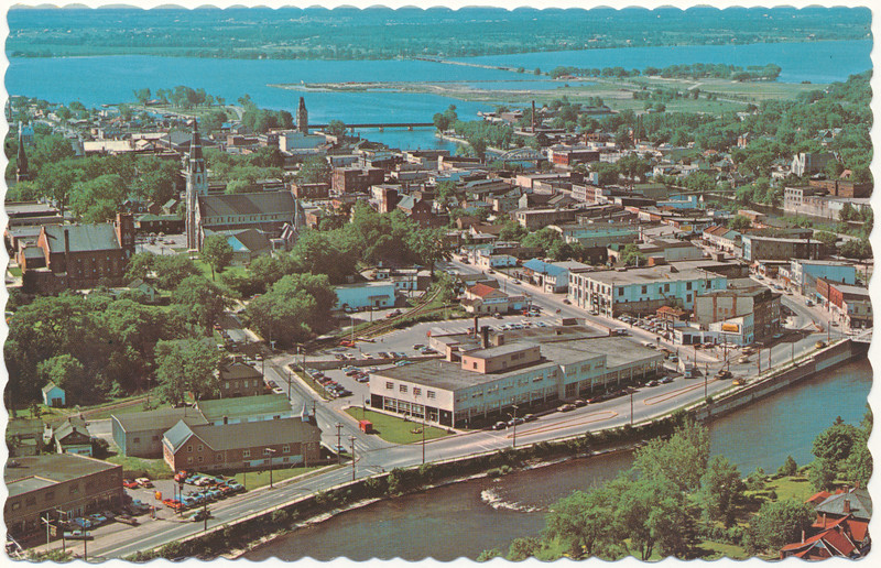 Postcard: A bird's eye view of Belleville, Ontario. Looking south from west side of the Moira over Federal Government Building on Station Street towards the Bay of Quinte. Photo by H. R. Oakman. Undated. Predates Dundas Street and Pinnacle Street bridges. Tabernacle United Church still standing. Railway tracks cross Church Street, may not go on to Pinnacle Street. Likely mid to late 1960s.