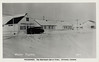 Postcard. Moosonee. The northern end of steel. Winter Traffic. 58-1. Showing Hudson's Bay store on Revillon Road, three houses past it (two weather station and one Hudson's Bay Company) and Moosonee lodge.
