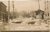 "Postcard: Belleville, Ontario. Bridge Street West facing West. Undated. Flooding, ice chunks on street. Looking up the West Hill. Back of card says ""Seven miles from Jack's home"""