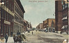 Postcard: Belleville, Ontario. Front Street looking north from Queen's Hotel and City Hall. Queen's Hotel sign overhanging sidewalk, horse drawn vehicles, Undated, not used. Holes and damage in corners, removed from album.