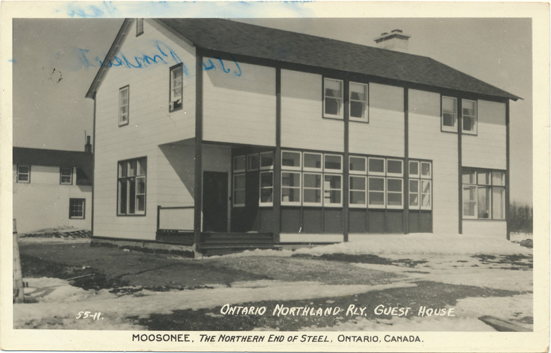 Postcard: Moosonee. Ontario Northland Railway Guest House. Marked 55-11. Shows left section of what became Moosonee Lodge plus one building behind it. Mailed from Moosonee August 8, year not clear, stamp may have been removed. Sent to Mr. Walter Hall, West Orange, N.J. Front of card. Some blue ink stains.