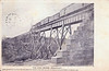 """Postcard """"The High Bridge, Englehart"""" mailed from Englehart, Ontario on May 30, 1908 showing railway bridge carrying the then Temiskaming and Northern Ontario Railway (now Ontario Northland) across the Englehart River. Image density enhanced but not retouched."""