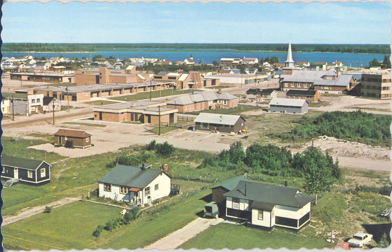 Moosonee, aerial view, could be from water tower. Showing railway houses, James Bay Educaton Centre, Bishop Belleau School before fire with flat  roof.