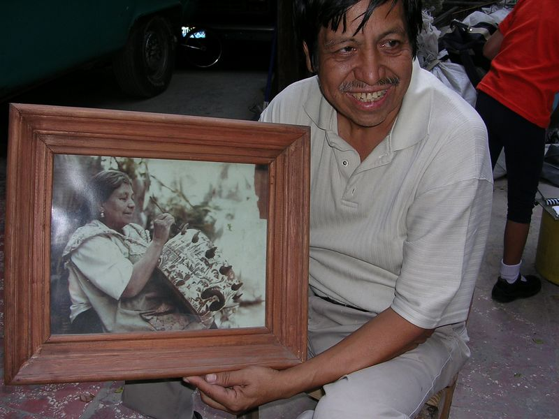 2/18/05 Santos Lucano holding a photo of his mother - wife of Balbino Lucano, who also painted.  Santos passed away in 2008.
