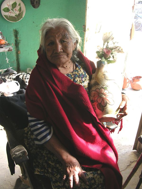 2/16/05 Maria Rosales, (90)  mother of Jesus Galan & Leonardo Galan, her husband was Jose Galan, her sister-in-law was Catalina Galan and her father-in-law was Bonifacio Galan.  Her son, Jesus made the vase she holds.  He is now blind & living in California.