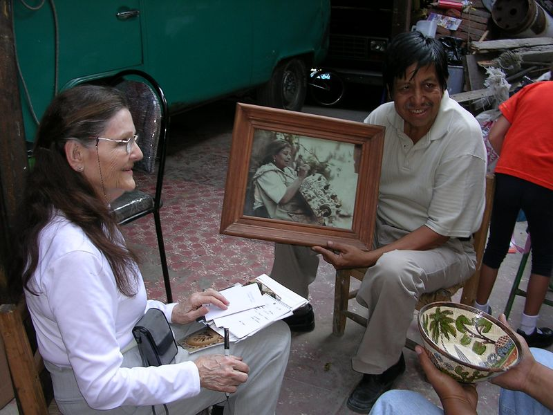 2/18/05 Lenore in the workshop of Santos Lucano.  He is holding a photo of his mother - wife of Balbino Lucano, who also painted.