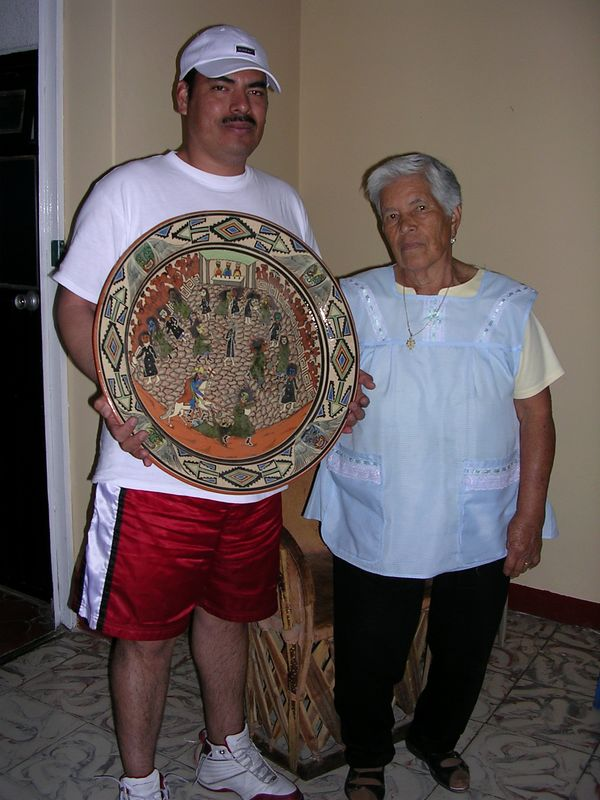 2/23/05 Maria Concepcion Arana Lucano and her son George holding a platter made by their family.  Her uncle was Balbino Lucano and her mother was Julia Lucano who also worked in petatillo for 52 years.