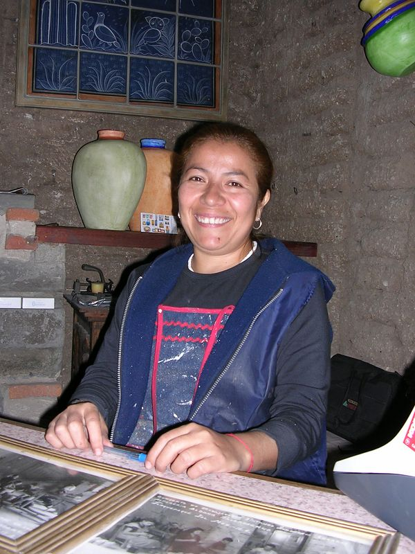 2/21/05 Maria Eugenia Rivera, grandaughter of Antonio Rivera, works in the shop next door to the Aldana family home for one of the Aldana daughters, Marta Elena.  Until only a few years ago there were 22 employees here, and now only two are left, Maria potting and painting and a packer.