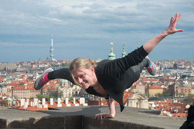 Girl doing crazy acrobatic stunts on the wall of Prague Castle which has a steep drop at the back. Prague, Czech Republic.