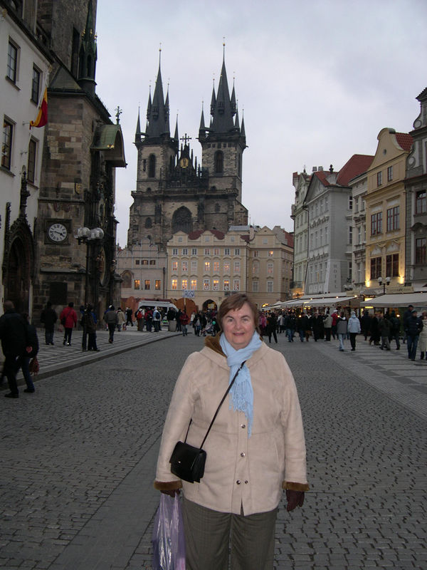 Susan in the Old Town Square of Prague, with the Tyn Church behind her.  Prague's famous clocktower is on the building to the left in the picture.