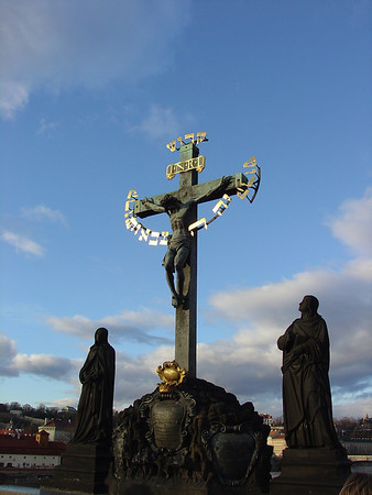 The statue of The Crucifix and Calvary, is one of the most historically interesting sculptures on the bridge, which gradually gained its present appearance throughout many centuries. The original wooden crucifix was installed at this place soon after 1361 and probably destroyed by the Hussites in 1419. A new crucifix with a wooden corpus was erected in 1629 but was severely damaged by the Swedes towards the end of the Thirty Years' War. The remnants of this crucifix can be found in the lapidarium of the National Museum in Prague. This was replaced by another wooden Calvary which, in turn, was replaced with a metal version in 1657. Bought in Dresden, this crucifix was originally made in 1629 by H. Hillger based upon a design by W. E. Brohn. In 1666, two lead figures were added, but these were replaced in 1861 by the present sandstone statues by Emanuel Max, portraying the Virgin Mary and John the Evangelist.<br /> The golden hebrew text on the crucifix was added in 1696. It was placed there as punishment for a Prague Jew, Eliass Backoffen, who has been convicted of debasing the Holy Cross. The text is derived from the words of the prophet Isaiah and reads, in English, Holy, holy, holy is the Lord of Hosts. These words, which are the origin of the Sanctus in the Mass, are an important confession of faith in the Jewish tradition as well; their placement in this context has been perceived by some as offensive. A bronze tablet with explanatory text in Czech, English and Hebrew was mounted under the statue by the city of Prague authorities in 2000. The tablet's placement came after an American Rabbi, Ronald Brown of Temple Beth Am in Merrick, New York was passing over the bridge and noted the possible offenses which could be misconstrued from the statue. Upon a direct request to the mayor, the tablet was soon placed in front of the statue. (wikipedia). © 2005 JOANNE MILNE SOSANGELIS, All rights reserved