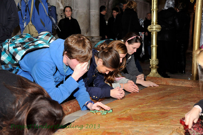 This slab of marble has traditionally been venerated as the place where they hastily wrapped Christ body with the shroud.  Christians venerate this spot, the 13th Station, praying for those in need, and place religious articles to be blessed. Once again, a moving spot for our students.