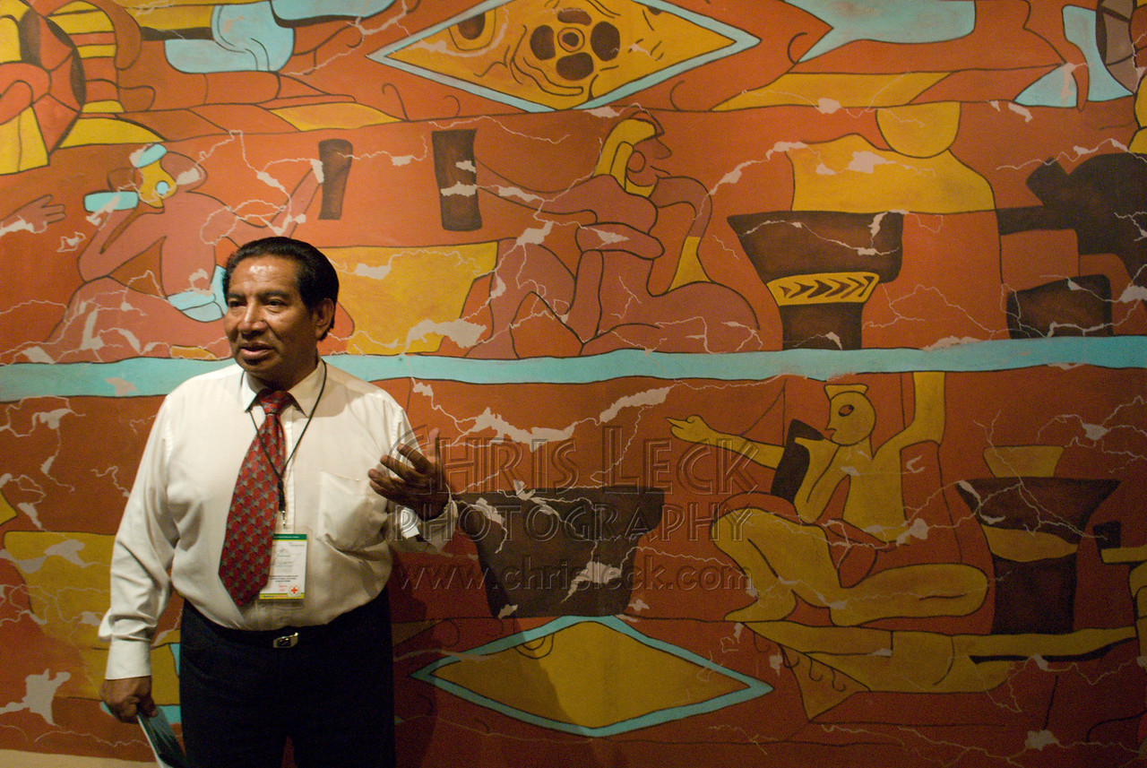 "Guide Alfredo Torres Cuahite lectures on the ""Mural of the Drinkers."" The original mural is found in a building from the Cholula II phase."