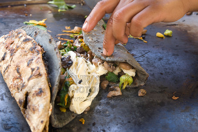 Street vendor making blue corn quesadillas with mushrooms, squash blossoms, and fresh cheese in El Parián