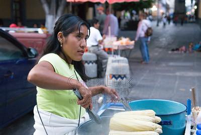 A street vendor boils ears of corn