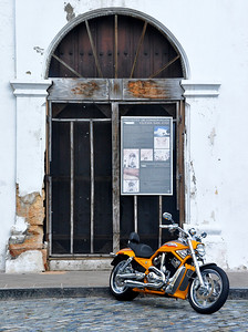 Church undergoing renovation with Motorcycle outside.