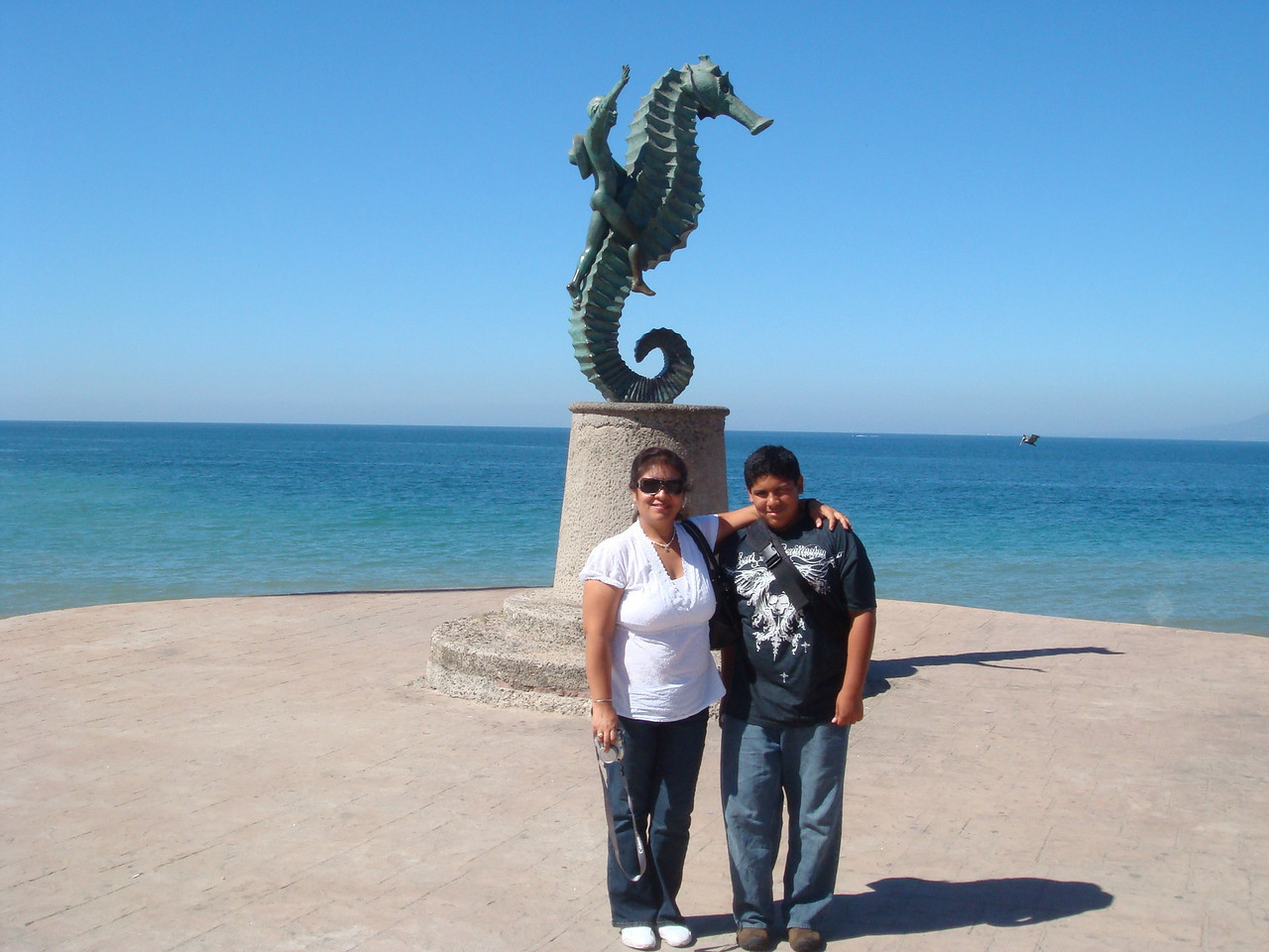Mom and son posing in front of the sculpture that characterizes Puerto Vallarta.<br /> <br /> La mama y el hijo, en frente de la escultura que caracteriza la ciudad de Puerto Vallarta.