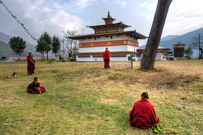 "Monks at the Temple of Fertility (Chimi L'hakhang Temple), Punakha, Bhutan. The site was blessed by the ""Divine Madman"" the maverick saint Drukpa Kunley (1455–1529) who built a chorten on the site. In founding the site it is said that Lama Kunley subdued a demon of Dochu La with his ""magic thunderbolt of wisdom"" and trapped it in a rock at the location close to where the chorten now stands. He was known as the ""Mad Saint"" or ""Divine Madman"" for his unorthodox ways of teaching Buddhism by singing, humour and outrageous behaviour, which amounted to being bizarre, shocking and with sexual overtones. He is also the saint who advocated the use of phallus symbols as paintings on walls and as flying carved wooden phalluses on house tops at four corners of the eves. The monastery is the repository of the original wooden symbol of phallus that Kunley brought from Tibet. This wooden phallus is decorated with a silver handle and is used to bless people who visit the monastery on pilgrimage, particularly women seeking blessings to beget children. The tradition at the monastery is to strike pilgrims on the head with a 10 inch (25 cm) wooden phallus (erect penis). Traditionally symbols of an erect penis in Bhutan have been intended to drive away the evil eye and malicious gossip. Temple of fertility is dedicated to the Lama Drukpa Kunley, the 'Divine Madman', decorated with colourful phalluses and visited by childless couples seeking a special blessing to beget children. This is one of the highly revered temples in all of Bhutan."