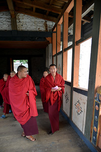 "Monks on the bridge linking to The Punakha Dzong, also known as Pungtang Dechen Photrang Dzong (which means ""the palace of great happiness or bliss""), is the administrative centre of Punakha District in Punakha, Bhutan."