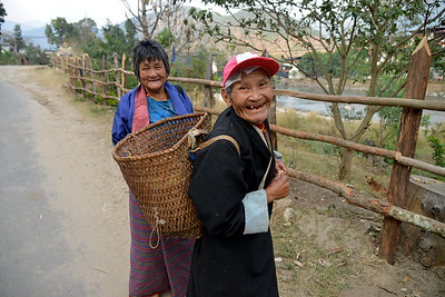 Old couple happy to show us the fresh oranges that they were carrying in the basket near the entrance of the Punakha Dzong (the palace of great happiness or bliss). Punakha, Bhutan.