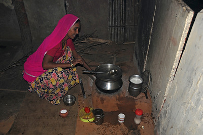 Sayar Singh's wife preparing dinner in her rural kitchen at home in Chamunda Matha Road, Pushkar. The town of Pushkar is located 14 km North West of Ajmer. Pushkar is one of the oldest cities of India. It  has in recent years become a popular destination for foreign tourists. Pushkar, Rajasthan, India.