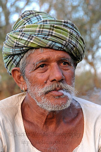 Sayar Singh's father smoking a beedi (like a cigarette) at their home in Chamunda Matha Road, Pushkar. The town of Pushkar is located 14 km North West of Ajmer. Pushkar is one of the oldest cities of India. It  has in recent years become a popular destination for foreign tourists. Pushkar, Rajasthan, India.