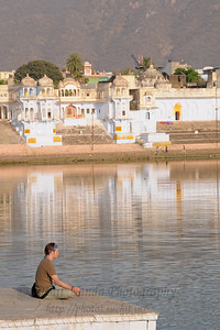 Meditating on the ghat of the holy Pushkar Lake. Many visit Pushkar for religious purposes.  The town of Pushkar is located 14 km North West of Ajmer. Pushkar is one of the oldest cities of India. It  has in recent years become a popular destination for foreign tourists. Pushkar, Rajasthan, India.